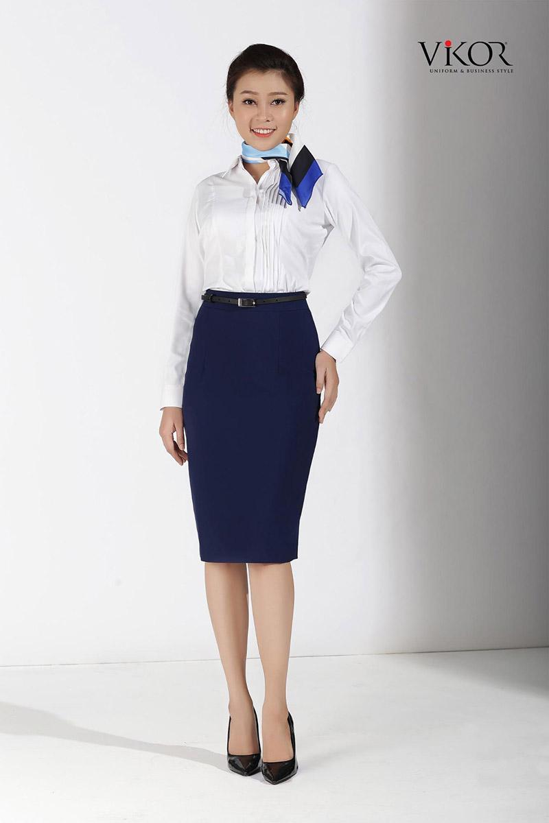 Phụ kiện khăn cổ màu xanh navy khiến tổng thể bộ đồng phục với sơ mi trắng kết hợp chân váy bút chì trở nên nữ tính và tinh tế hơn